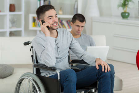 disabled young man talking on the phone at home