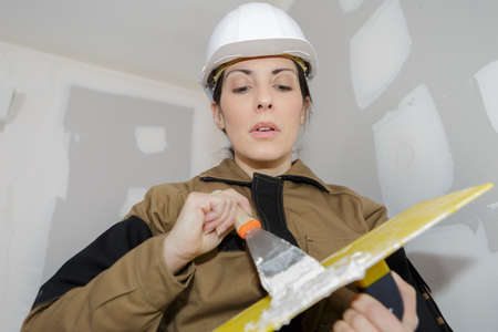 beautiful plasterer doing some indoor work Stock Photo