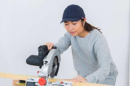 a thai girl carpenter is using a circular saw