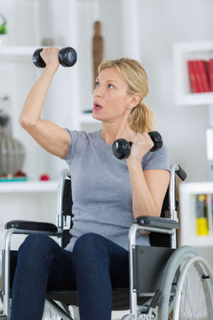 middle age patient in lifting dumbbell in clinic