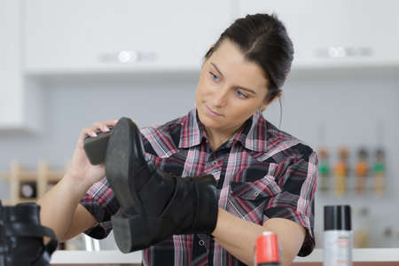 young woman cleaning shoes in her kitchen