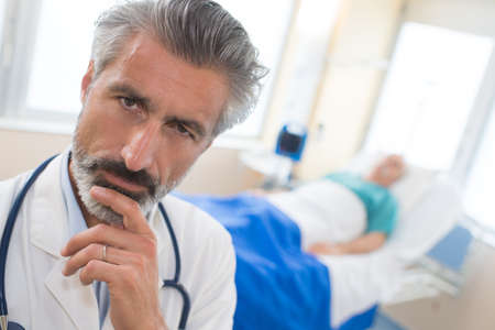 thoughtful doctor sitting at meeting in hospital