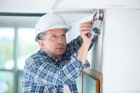 senior technician adjusting cctv camera on wall Stock Photo