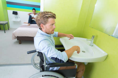 man on wheelchair washing hands in bathroom