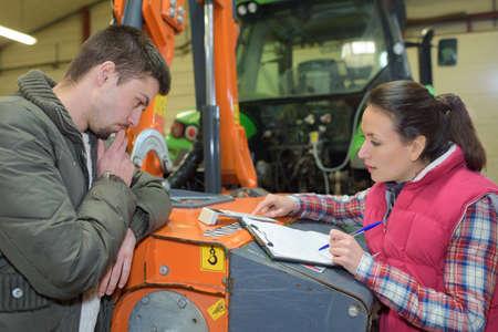 young cheerful farming couple checking their tractor before the harvest Stock Photo