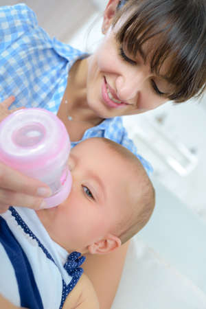 Mother bottle feeding baby