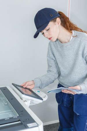 young woman technician maintaining printer Stock Photo