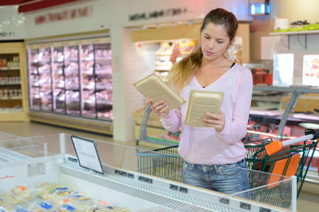 Woman in supermarket comparing two packs of food Stock Photo