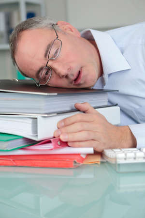 over-worked tired businessman at office sleeping at his desk Фото со стока