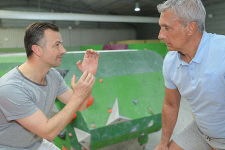 instructor giving advice to senior man by indoor climbing wall