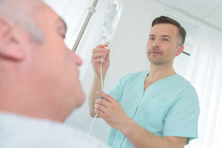 doctor examining intravenous drip in hospital Фото со стока