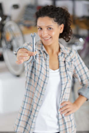 happy young woman showing a spanner while repairing bike Stockfoto - 123138340