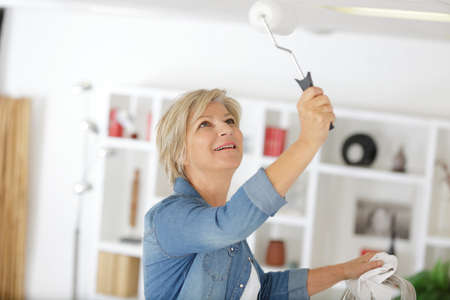 mature woman using roller to paint the ceiling 版權商用圖片