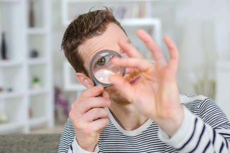 man looking at ring through magnifying glass