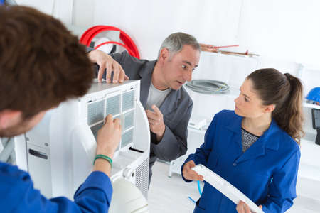 hvac repair technicians working on commercial heating air conditioning unit Stock Photo