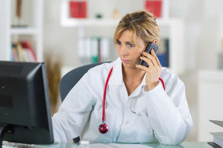 middle-aged female doctor on telephone while looking at computer