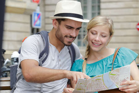 man with map shows the girl a direction Imagens