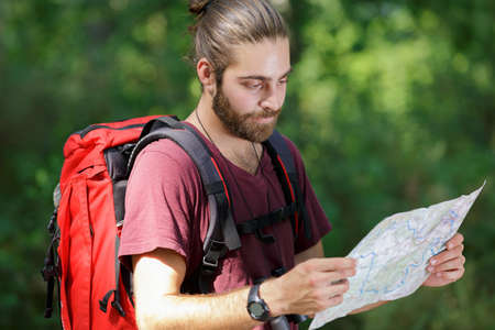 man in the countryside with backpack and map Stock Photo