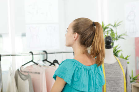young woman looking at clothes on clothes rail in store