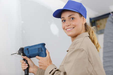 mid-adult woman drilling hole in wall
