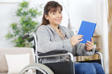 woman in wheelchair reading a book Stock Photo