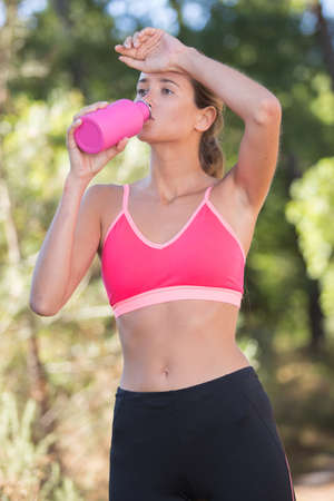 woman drinking water during exercise pause
