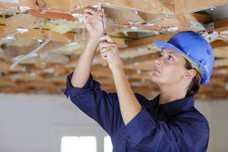 female manual worker using screwdriver on ceiling joist Reklamní fotografie