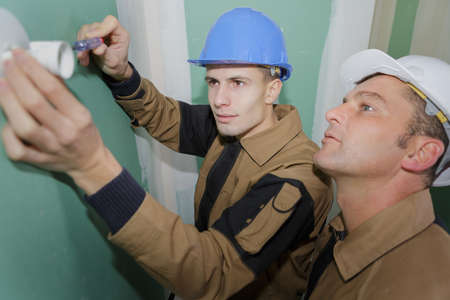 young electrician with screwdriver fixing socket
