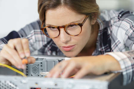 photo of woman fixing a broken pc