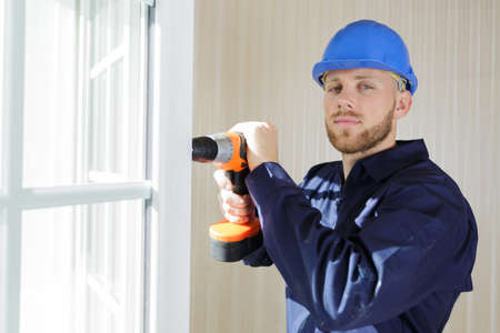 male builder using cordless drill on window