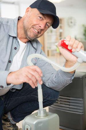 man filling oil tank at home Standard-Bild
