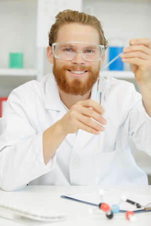 young interested scientist keeping and overlooking test tube