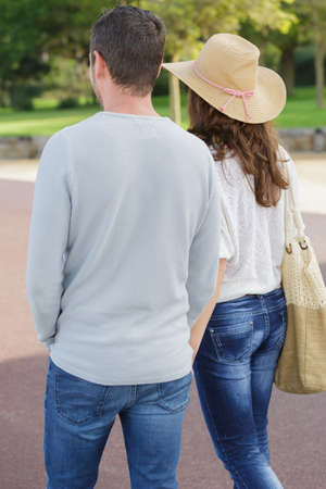 rear view of young couple walking in a park Imagens