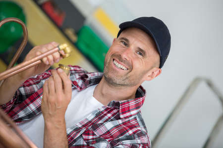 portrait of male plumber holding copper pipe and fittings Stock Photo