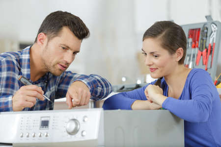 plumber installing water shutoff valve for washing machine at home Stockfoto