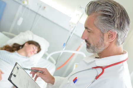 doctor reading notes of young woman in hospital bed