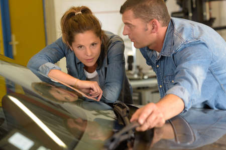 man and woman looking at windshield in garage Stock Photo