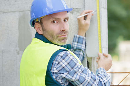 construction worker with measuring tool Stockfoto