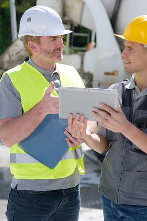 à l'aide d'une bétonnière sur chantier avec des apprentis