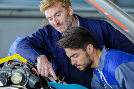 apprentice taking notes of engine parts Stock Photo