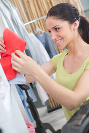 beautiful young woman buying clothes in modern shop 写真素材