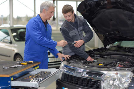 student mechanic learning from teacher in automotive vocational school