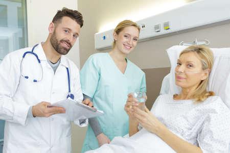 dottore seduto che assiste una paziente anziana sul letto? Archivio Fotografico