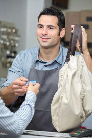 commis de sexe masculin prenant le paiement au comptoir de la boutique