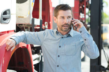man in casual outfit conversing in cellphone leaning on truck