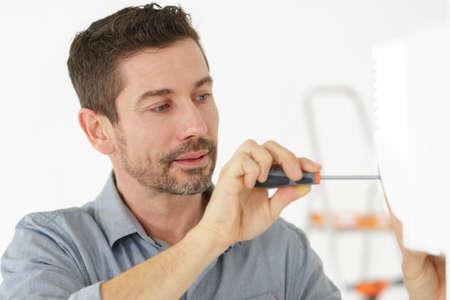 man using screwdriver on doorframe Standard-Bild