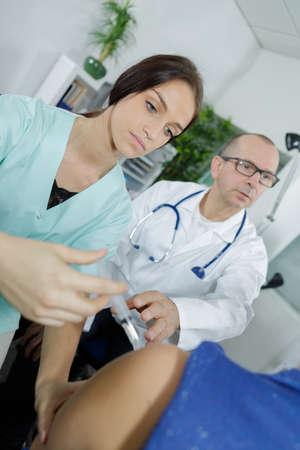 nurse injecting the patients shoulder
