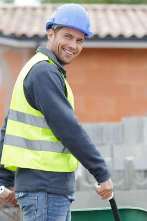happy construction worker pushing a wheelbarrow