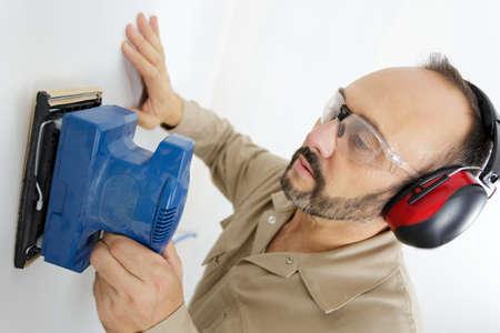 man sanding wall 写真素材