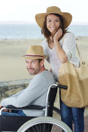 loving couple in wheelchair outdoors near seaside